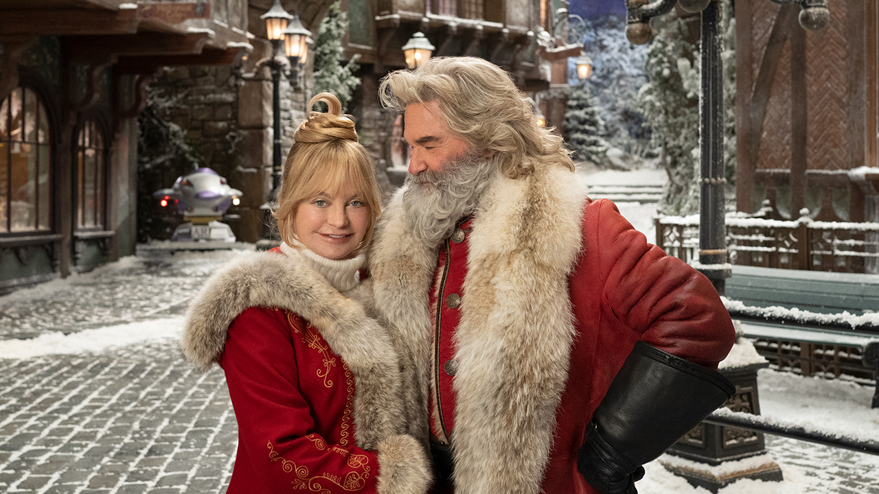 image of Santa claus and Mrs. Claus standing in a snowy village