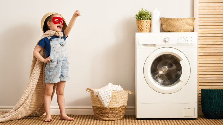 little kid wearing super hero outfit in the laundry room