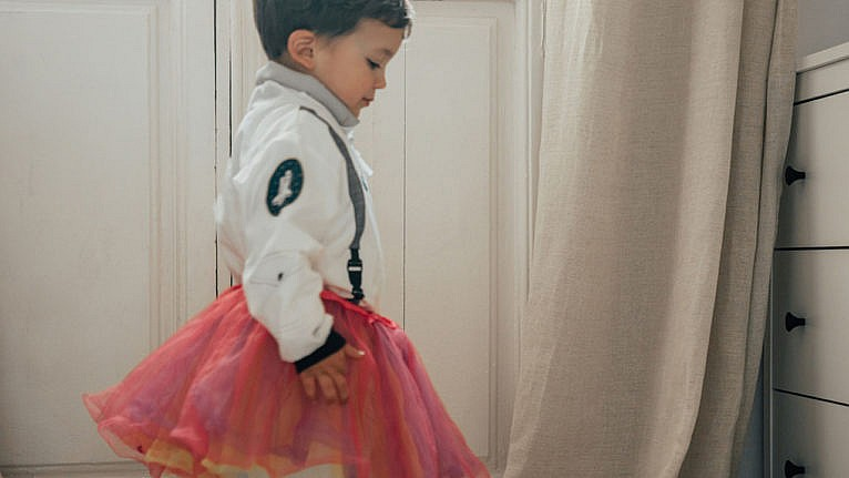 photo of a kid wearing an astronaut costume with a poofy pink tutu