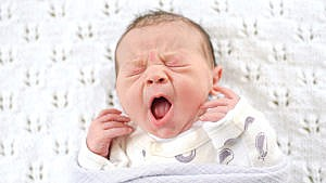 Why is my noisy newborn grunting, snoring and whistling in their sleep?