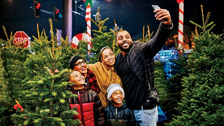 A family with their son, daughter and grandmother taking a selfie among Christmas trees