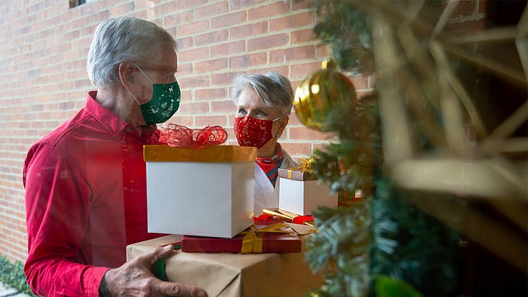 A photo of grandparents standing on a porch holding presents while wearing masks.