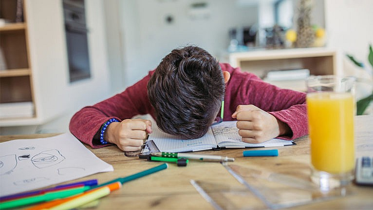 Photo of a kid with their head down in frustration on a notebook and their hands are balled into fists