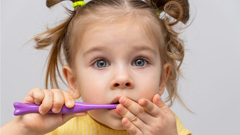 a nervous preschool-aged girl in a yellow shirt holds a purple toothbrush to her mouth
