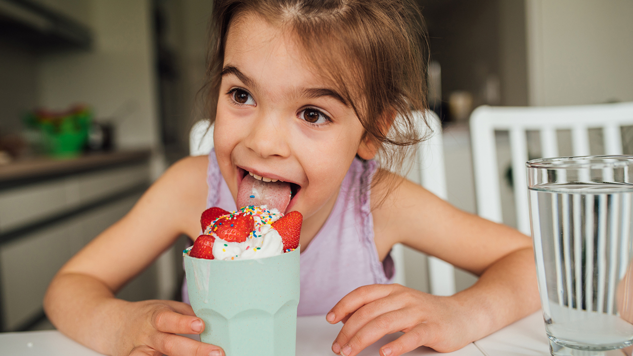 photo of a young kid joyously licking ice cream in a cup while sitting at the dinner table