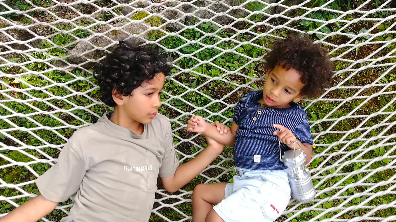 Photo of two brothers with curly hair lying down together on a hammock