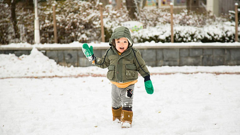 photo of a toddler playing in the snow