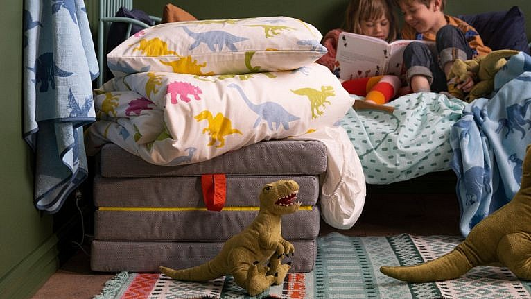 kids sitting on bed in dinosaur-themed room