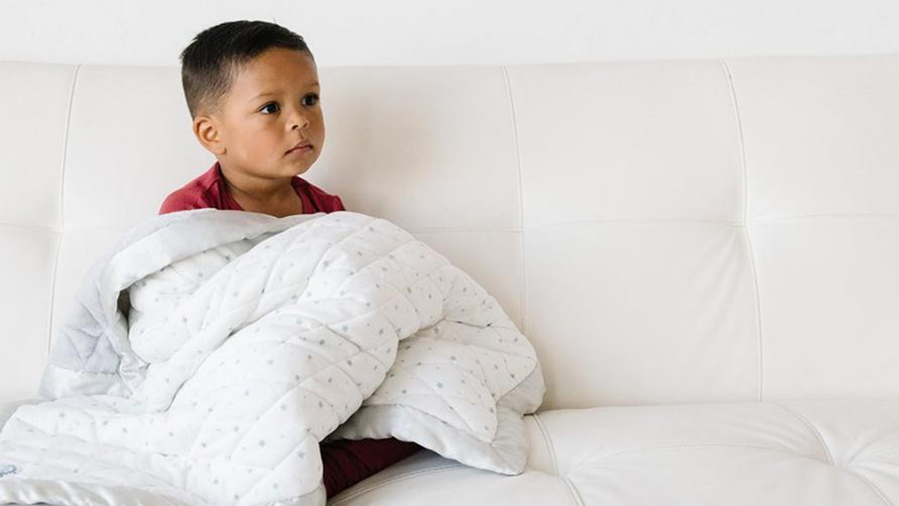 Photo of a kid sitting on a couch with a weighted blanket on their lap