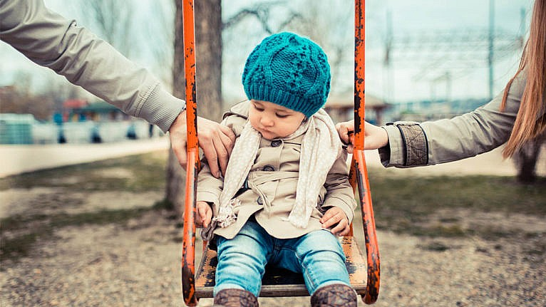 Photo of a child sitting on a swing wearing fall attire while their mom and dad hold each side of the swing making it look like a power struggle