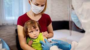 Photo of mom holding her child while they get a shot at the doctors office. The doctor is wearing full PPE.