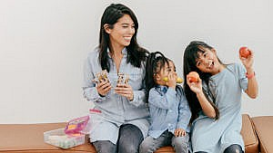 Trisha Enriquez and her two daughters holding snacks