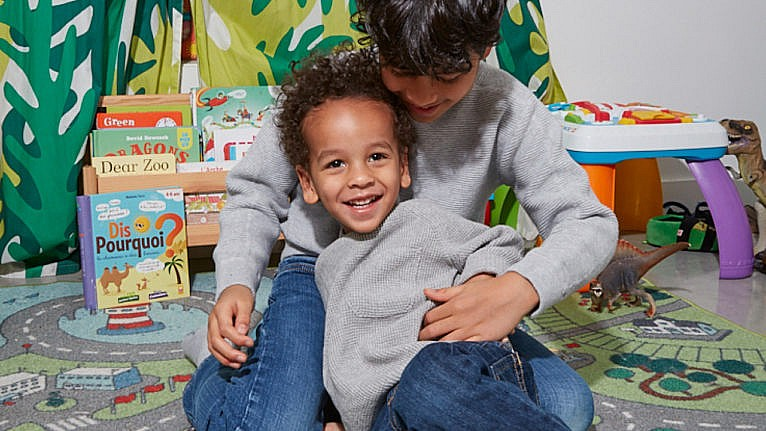Brothers in grey thermal long sleeve shirts and jeans snuggle in their play room-one has curly hair and one has straight hair for a story about them not being able to get their hair cut at the same salon