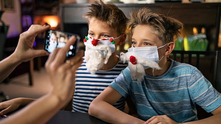 photo of a parent taking a picture of two kids wearing facemasks that have been decorated to look like santa's beard