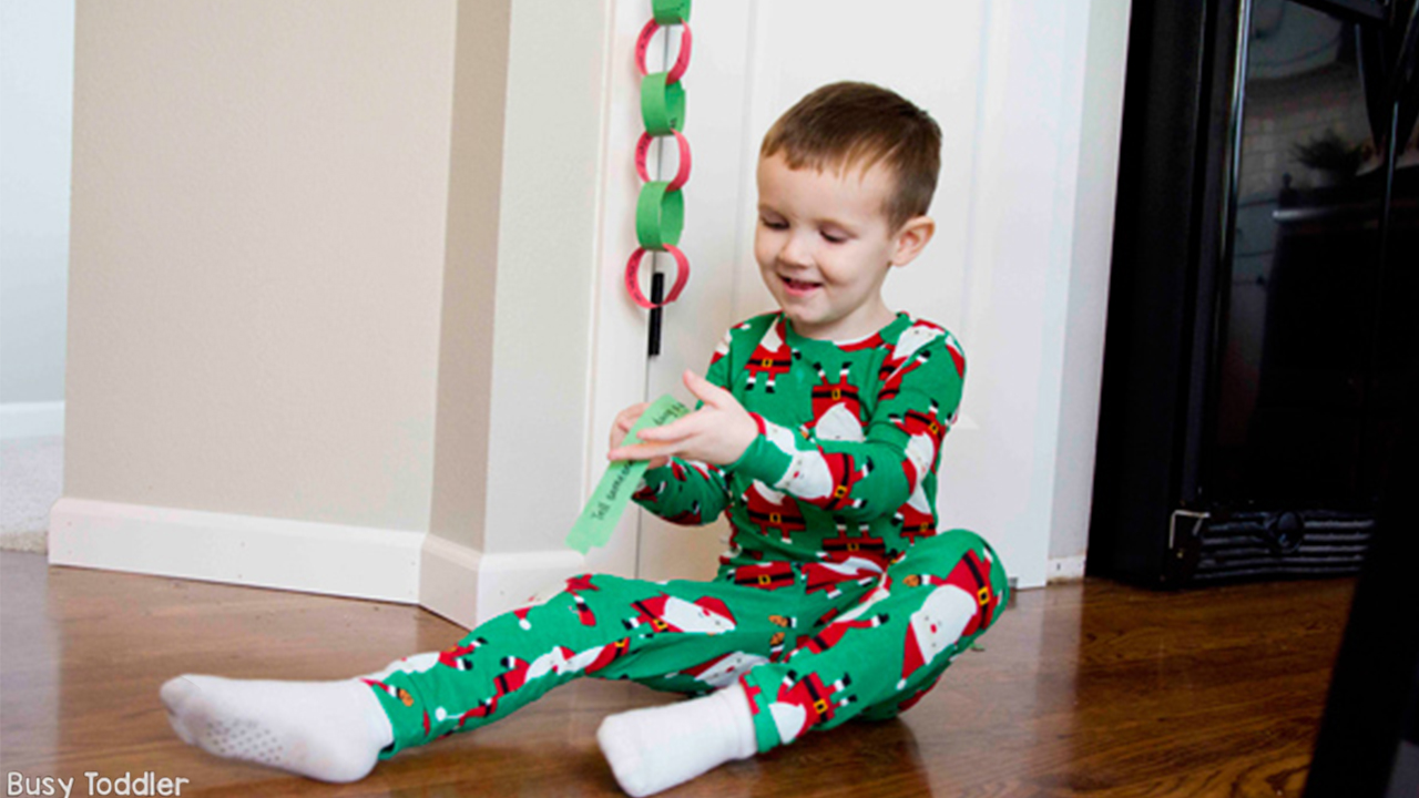 a photo of a kid in holiday pajamas reading off of a strip of paper that was a link on a paper chain