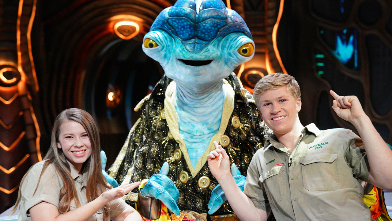 A still from the Disney+ show Earth to Ned showing a big blue alien posing for a picture with Steve Irwin's kids Bindi and Robert