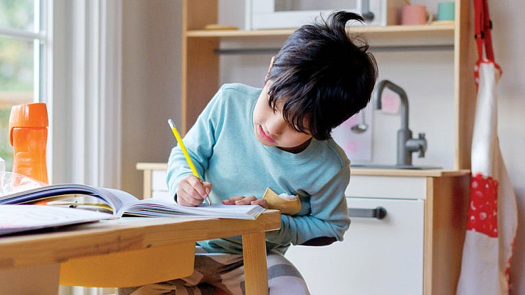 Photo of a kid sitting at a table practicing writing in a notebook