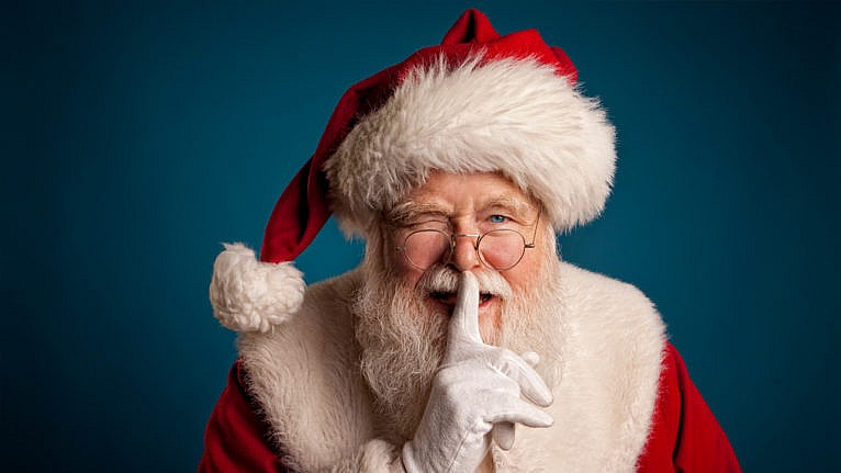 Santa in his red and white outfit and hat winking with his finger to his lips saying shhhh
