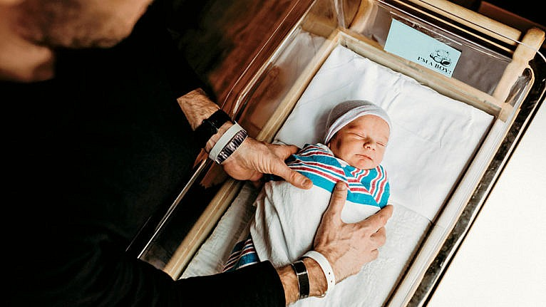 Photo of an adult placing a swaddled newborn in a bassinet at the hospital