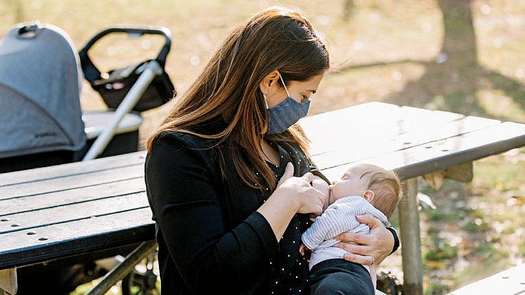 A mom in a mask nurses her newborn baby while sitting at a picnic table for a story on new moms not being ok during the pandemic