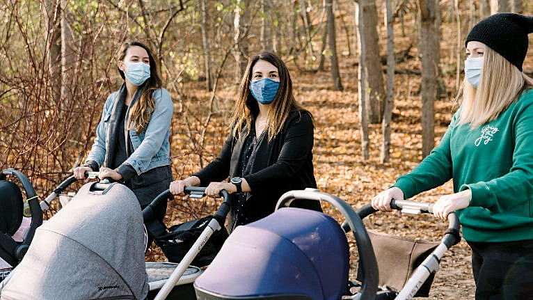 three moms walking in the woods wearing masks while pushing their strollers for a story on how new moms can feel less isolated during the pandemic