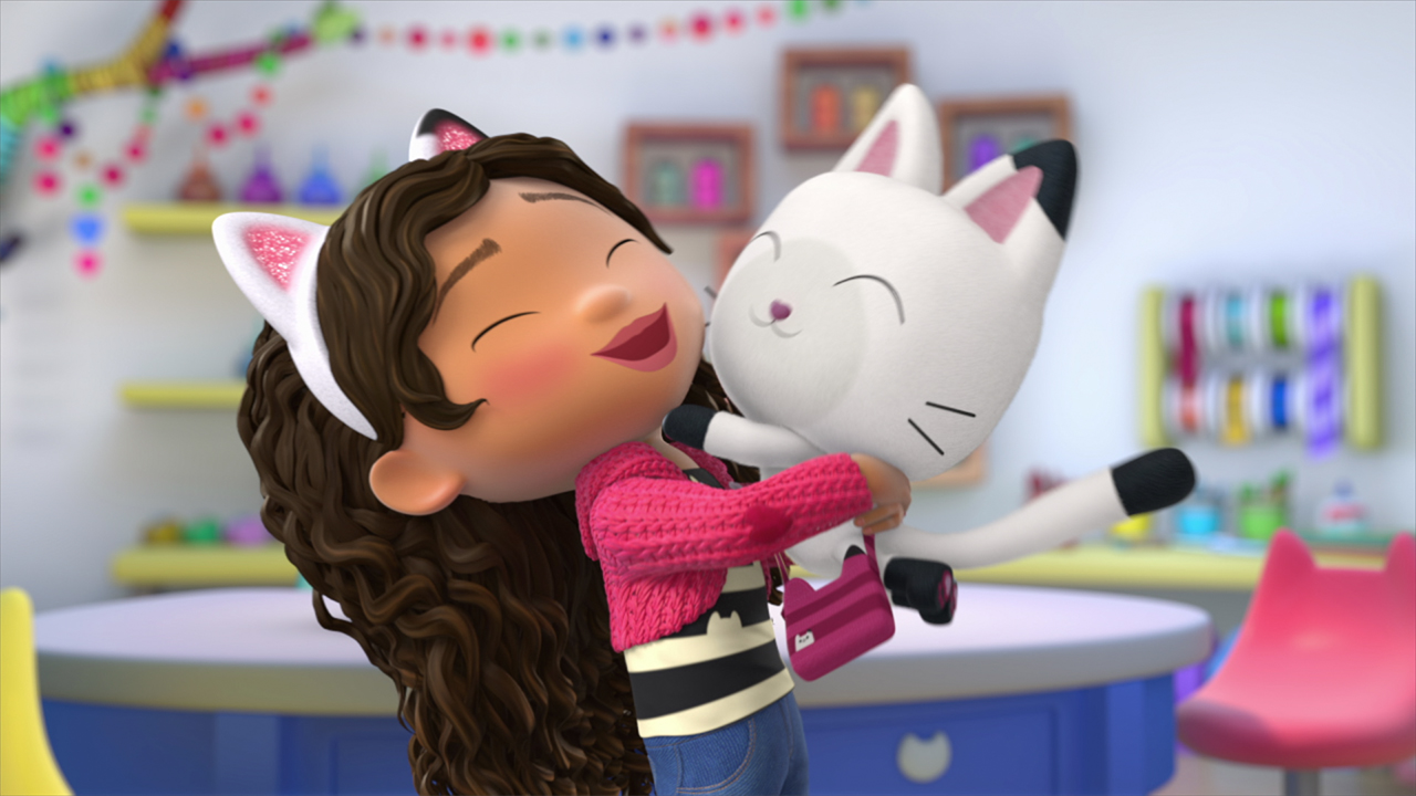 A still from the show Gabby's Dollhouse showing a kid with long curly hair hugging a cat in a crafting room