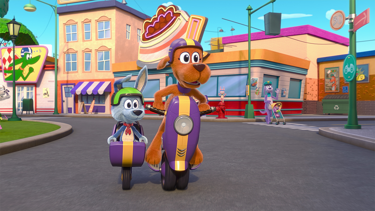 A still from the animated show Go Dog Go showing two dogs riding in a scooter and sidecar through town