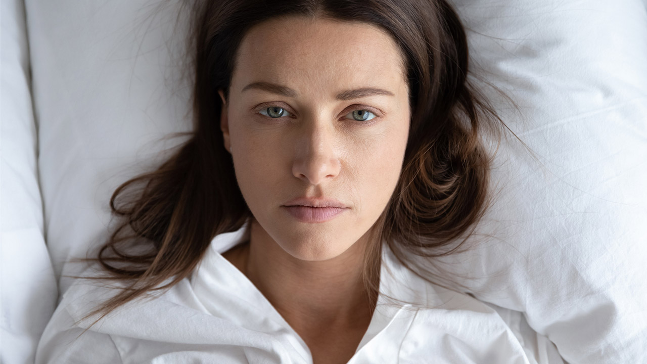 A photo of a woman lying in bed that only shows her from the neck up. She has a sad expression on her face