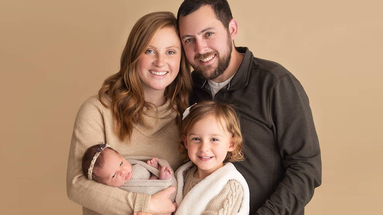 A family portrait showing a couple with their two kids, one is a preschooler and the other is a newborn baby