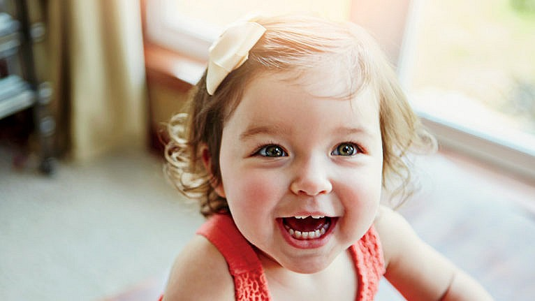 a close up of a smiling toddler with a bow in her hair and a chipped front tooth for a story on what to do if you toddler chips, cracks or knocks out a baby tooth