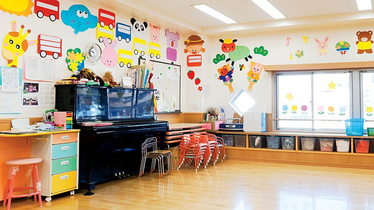 An empty daycare classroom with little chairs stacked and bins tucked into cubbies under the window with cutouts of bright animals and buses on the walls for a story about daycare closures