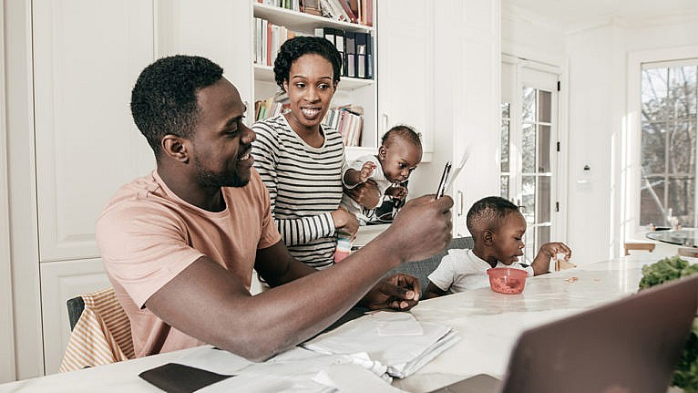 Photo of a Black couple doing financial work in their kitchen while caring for their two children