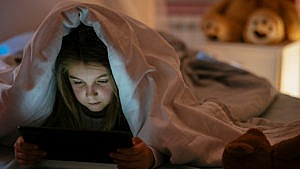 Photo of a kid in bed playing with a tablet under the covers