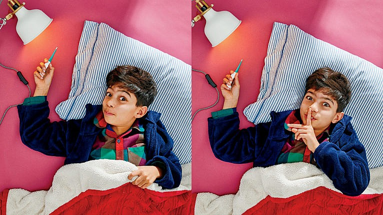 Photo of a kid laying in bed while holding a thermometer up to a light bulb and a finger to his mouth saying shhh
