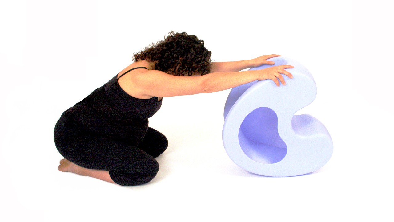 woman stretching over birthing stool