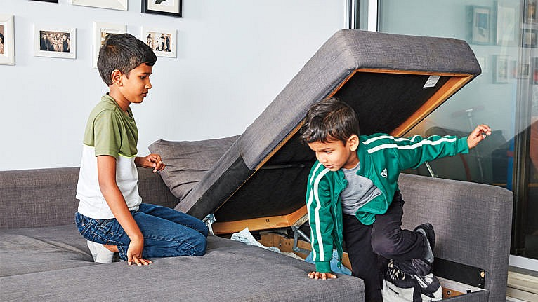 Photo of two kids putting things away in the storage underneath the sofa