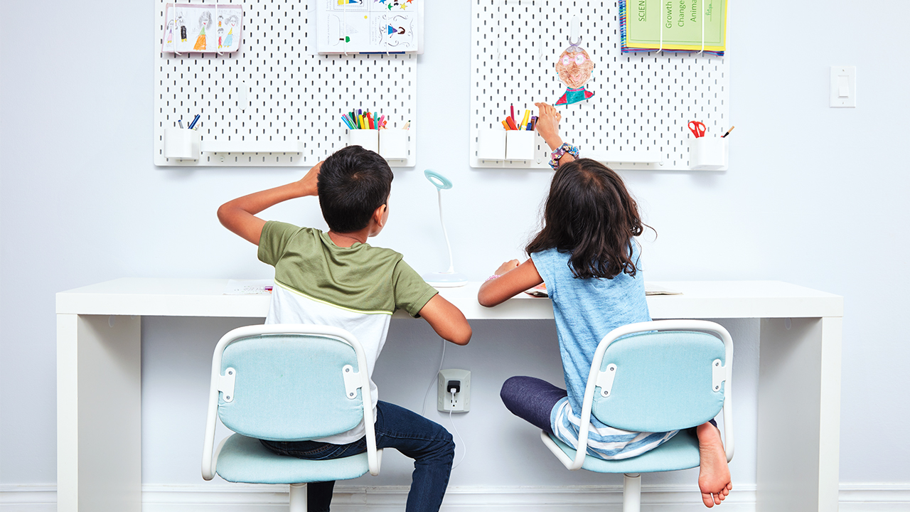 photo of two kids sitting at a desk reaching for pencils that are hung up on the wall