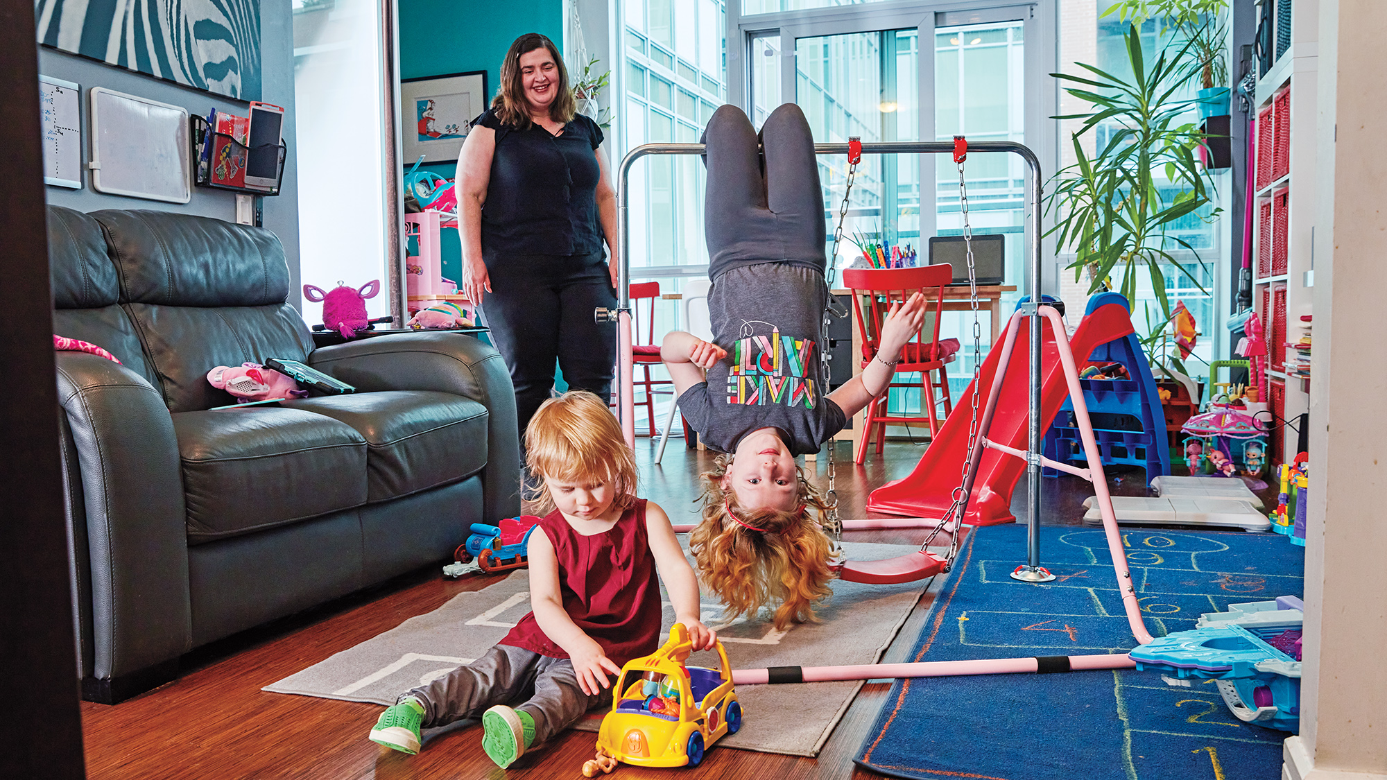 Photo of a single mother and her two kids playing in the living room on a mini swing set
