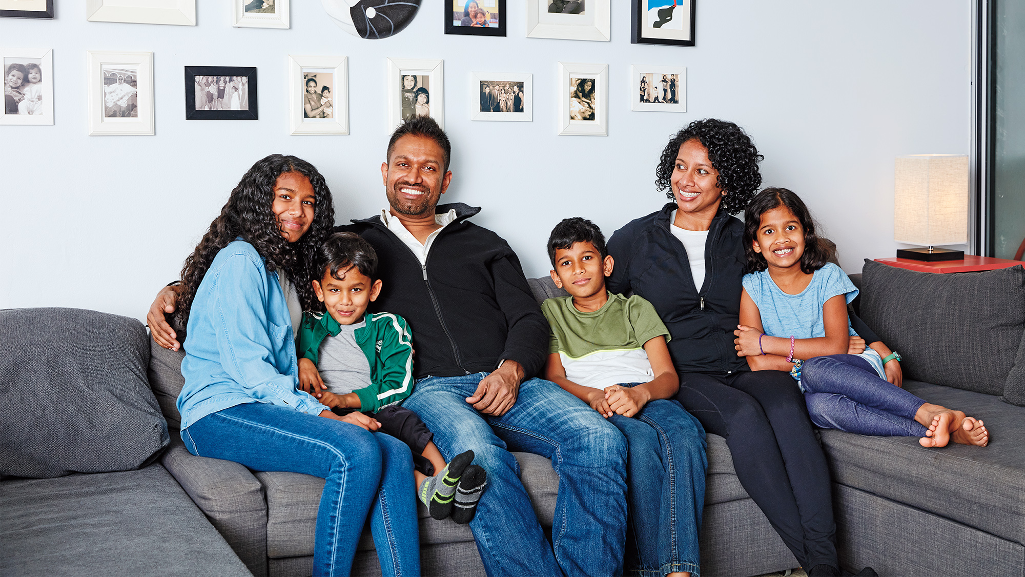 Photo of a family of six sitting on a sofa in their living room