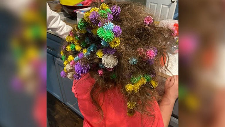 Photo of a kid with multiple brightly coloured toys tangled in her hair