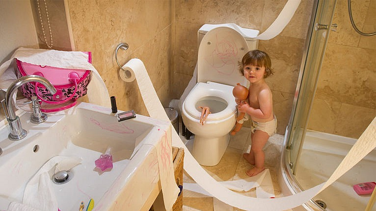 photo of a toddler in a diaper making a big mess in the bathroom. Toilet paper is unraveled, There are make-up drawings all over the sink and toilet and a doll is sticking out of the toilet bowl