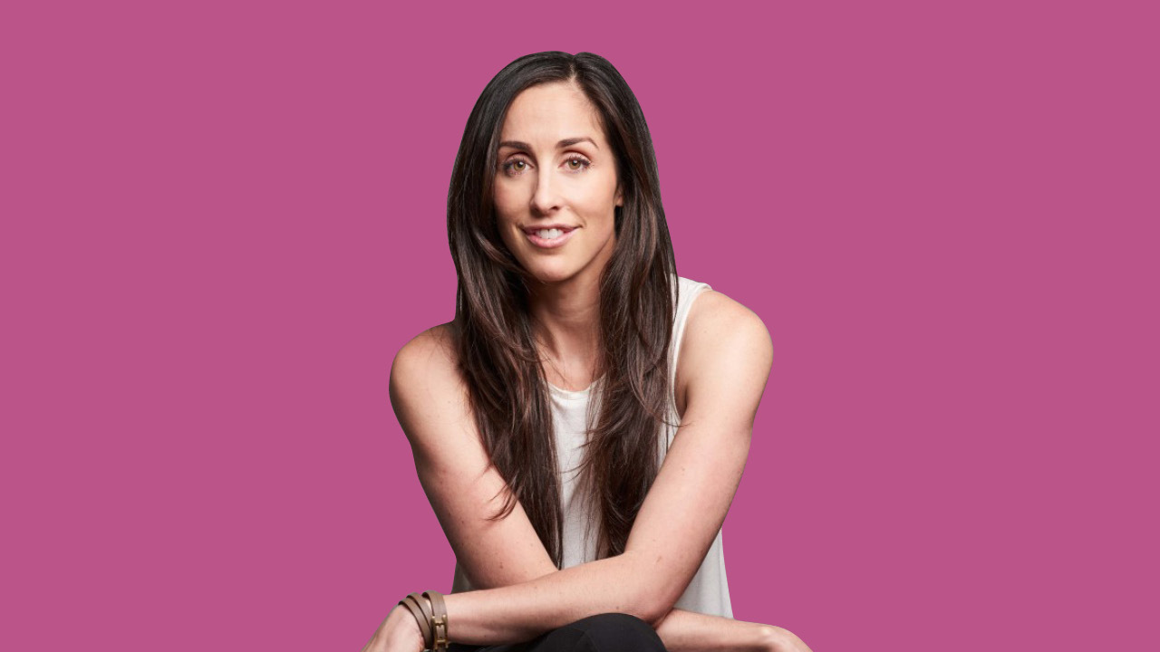 Catherine Reitman sitting in front of a pink background
