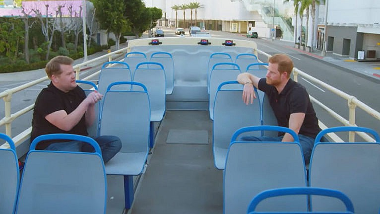 Still of James Corden and Prince Harry talking while riding through Los Angeles on a double decker bus