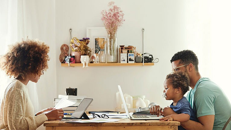 Photo of a couple working at the kitchen table. One of them carries a baby sucking on a pacifier while they work on a laptop
