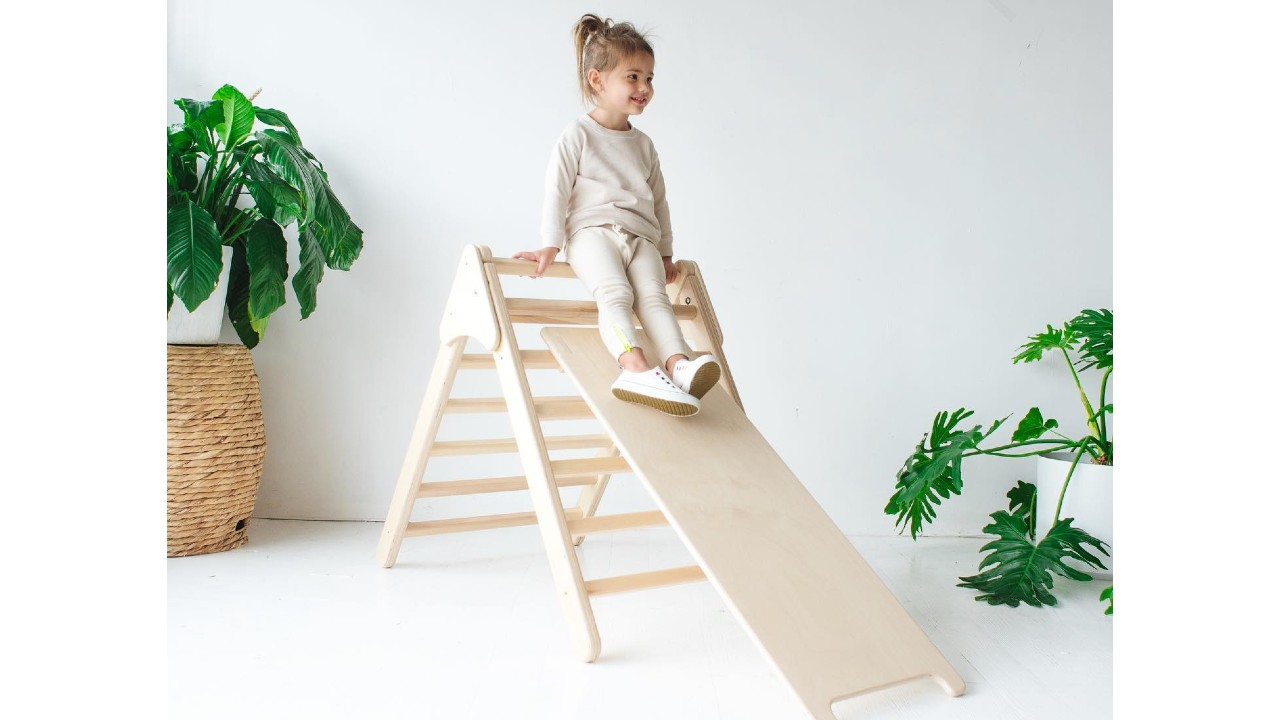 girl sliding down wooden indoor play structure