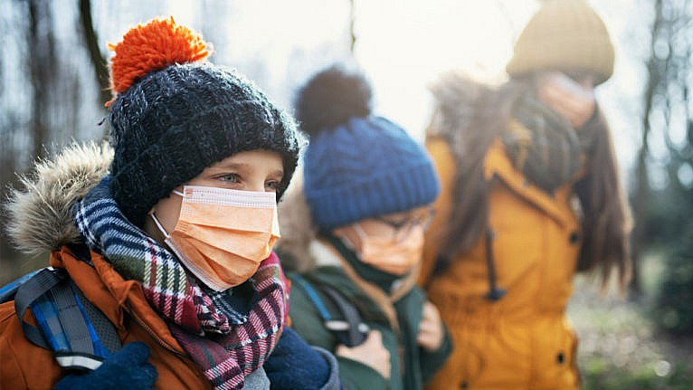 Two kids in toques, backpacks and masks walk to school with their mom for a story on schools not getting any safer ahead of the third wave