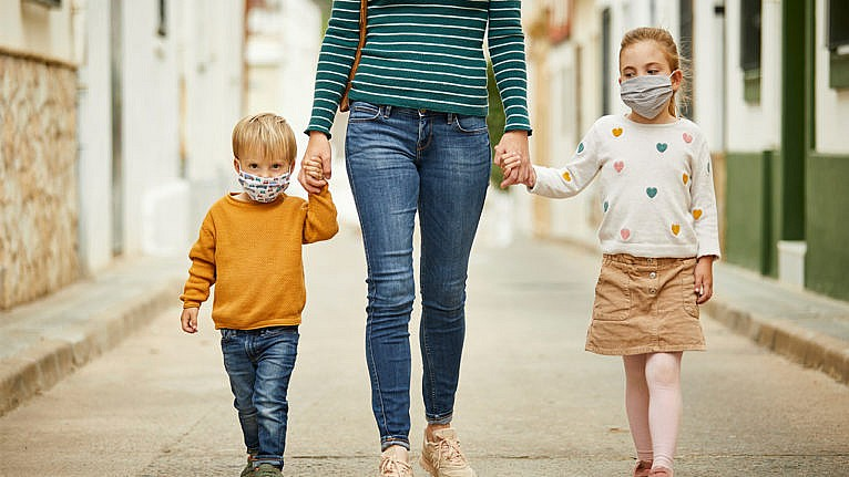Photo of a mom and two kids walkiing down a street wearing masks