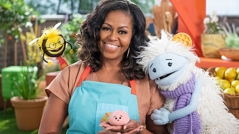 Promo photo from Michelle Obama's new netflix show Waffles and Mochi showing Michelle posing with three puppets. One is a yeti wearing a scarf with a waffle on their head, another is a bee wearing glasses and a necktie and the last is a little pink ball of mochi