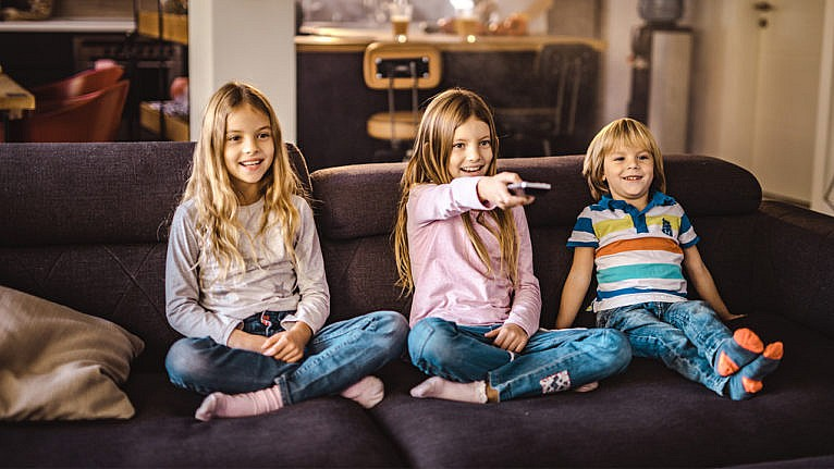 three kids aged around four to nine sit on the couch watching tv for a story on dealing with screen time guilt