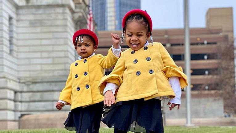Photo of two sisters dressed up in yellow coats and red headbands to honour Amanda Gorman for Black History Month